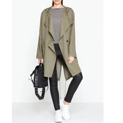 דוגמנית לבושה מעיל גשם בצבע בז' של אול סיינטס All Saints ואוחזת תיק מנהלים שחור